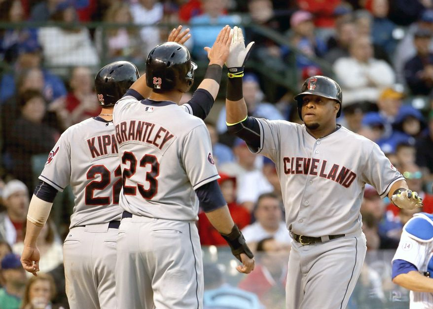 Cleveland Indians' Carlos Santana, right, celebrates his three-run home run off Chicago Cubs starting pitcher Jake Arrieta, with Jason Kipnis, and Michael Brantley (23) during the third inning of an interleague baseball game Tuesday, June 16, 2015, in Chicago. (AP Photo/Charles Rex Arbogast)