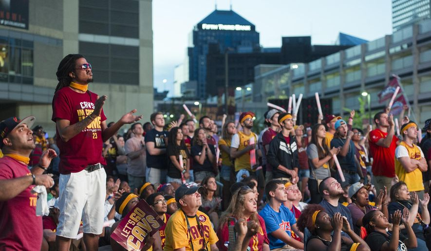 Brian Page, top left, cheers while watching on a big screen outside Quicken Loans Arena as the Cleveland Cavaliers play the Golden State Warriors inside the arena, during Game 6 of basketball's NBA Finals in Cleveland, Tuesday, June 16, 2015. (AP Photo/Phil Long)