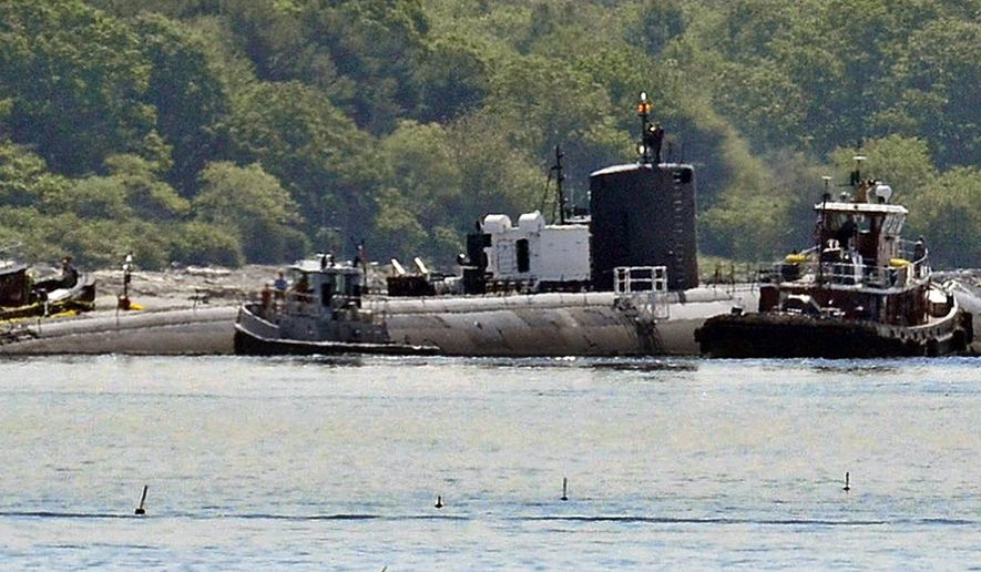 In this Friday, June 12, 2015 photo provided by the U.S. Navy, tugs assist as the former USS Miami nuclear-powered submarine is towed from the Portsmouth Nasal Shipyard in Kittery, Maine. The sub was heavily damaged  in 2012 by a fire set by a shipyard worker who pleaded guilty to setting the fire and is serving a 17-year prison sentence. The sub is being towed to to Puget Sound Naval Shipyard, where it will be dismantled as scrap. (Jim Cleveland/U.S. Navy via AP)