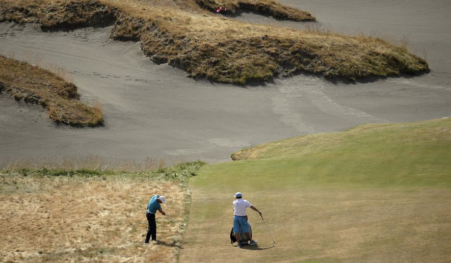 Martin Kaymer, left, of Germany, hits from rough on the fifth hole during a practice round for the U.S. Open golf tournament at Chambers Bay on Tuesday, June 16, 2015 in University Place, Wash. (AP Photo/Charlie Riedel)