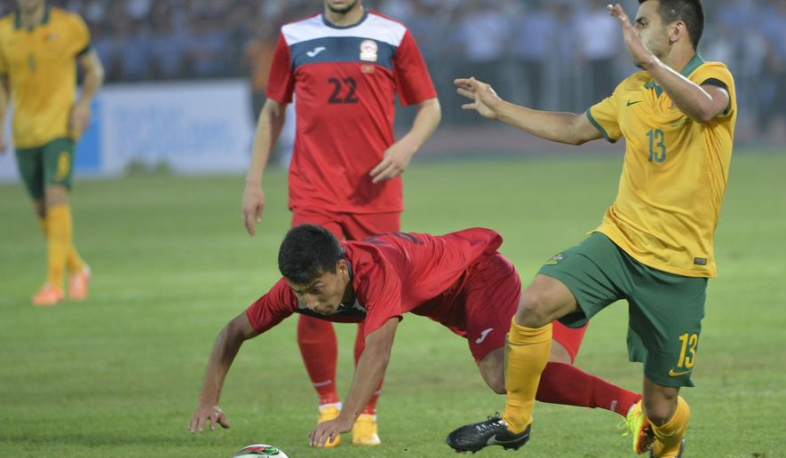 Australia's Aziz Behich, right, fights for the ball with Kyrgyzstan's Farhat Musabekov and Kyrgyzstan's Anton Zemlianukhin, background centre,  during the 2018 World Cup qualifying  Round 2 Group B soccer match between Kyrgyzstan and Australia in  Bishkek, Kyrgyzstan, Tuesday, June 16, 2015. (AP Photo/Vladimir Voronin)