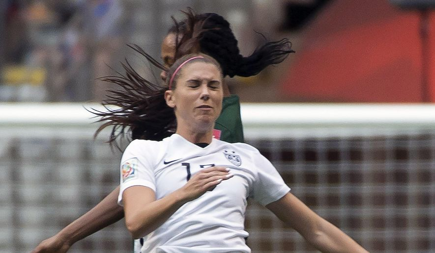 United States' Alex Morgan fights for control of the ball with Nigeria's Onome Ebi during the second half of a FIFA Women's World Cup soccer match, Tuesday, June 16, 2015 in Vancouver, New Brunswick, Canada (Jonathan Hayward/The Canadian Press via AP) MANDATORY CREDIT