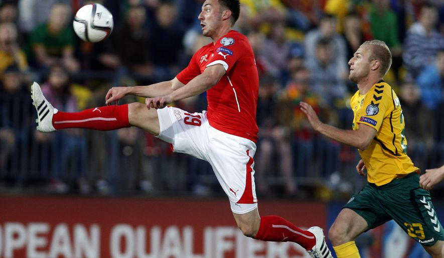 Lithuania's Vytautas Andriuskevicius , right, and Switzerland's Josip Drmic  challenge for the ball during the Euro 2016 group E qualifying soccer match between the Lithuania and Switzerland at the LFF stadium in Vilnius, Lithuania, Sunday, June 14, 2015. (AP Photo/Mindaugas Kulbis)