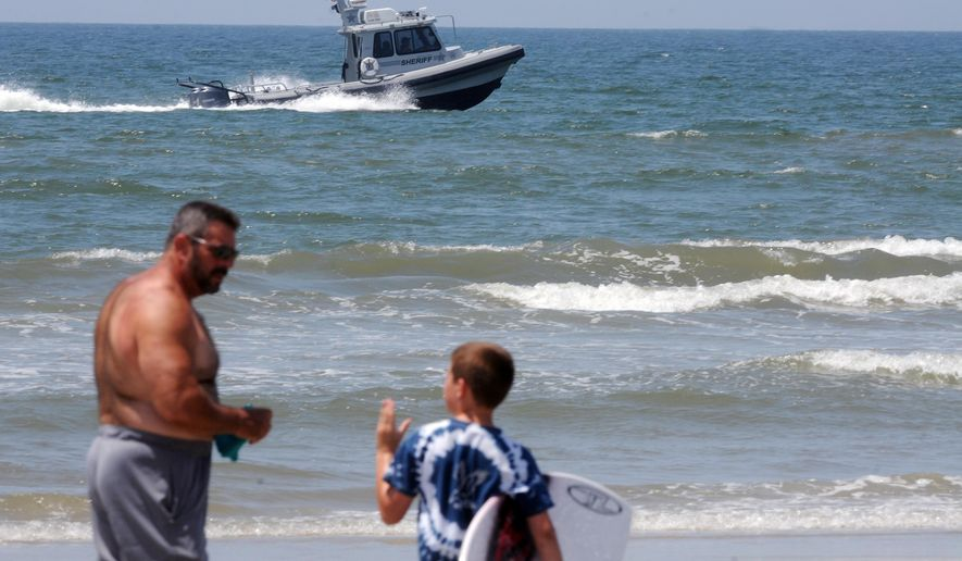 Jack Cross, 9, watches as a boat patrols the coastline near Ocean Crest Pier in Oak Island, N.C., Monday, June 15, 2015. Beachgoers cautiously returned to the ocean Monday after two young people lost limbs in separate, life-threatening shark attacks in the same town in North Carolina. (Mike Spencer/The Star-News via AP)  LOCAL TELEVISION OUT; LOCAL INTERNET OUT