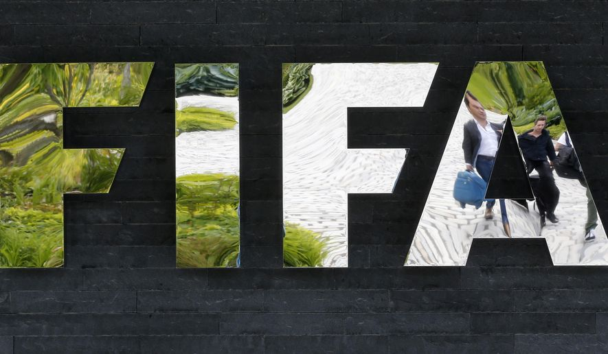 FILE - In this May 27, 2015 file photo two persons are reflected in the FIFA logo at the FIFA headquarters in Zurich, Switzerland. Swiss Attorney-General Michael Lauber said in a press conference Wednesday, June 17, 2015 that banks have noted 53 possible money-laundering cases in a FIFA probe.  (AP Photo/Michael Probst, file)
