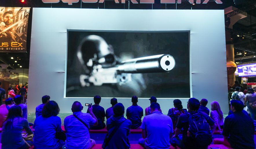 """Attendees watch a Square Enix """"Hitman"""" video game at the E3 Electronic Entertainment Expo at Los Angeles Convention Center on Tuesday, June 16, 2015. (AP Photo/Damian Dovarganes)"""