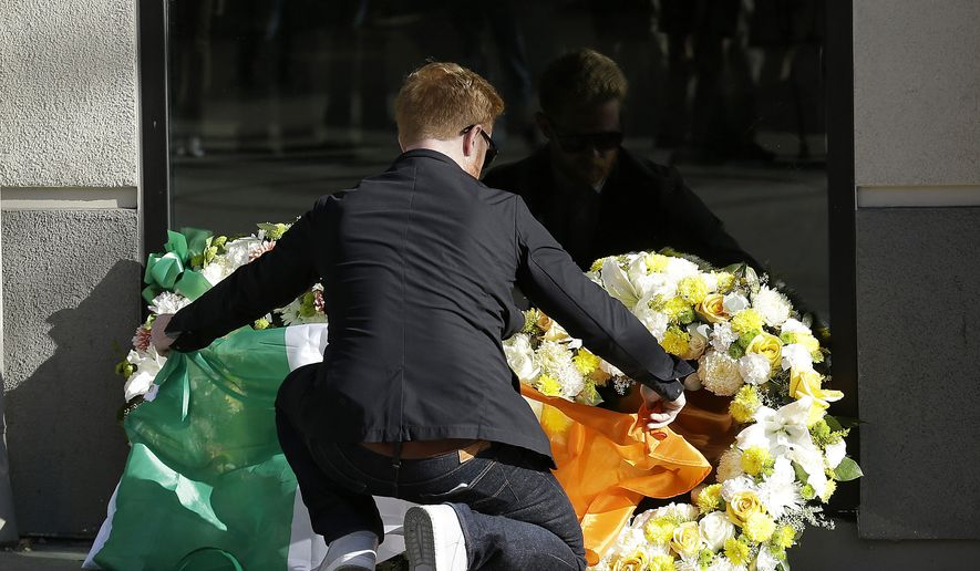 Neil Sands of the Irish Network Bay Area places a flag of Ireland over wreaths at the Library Gardens apartment complex in Berkeley, Calif., Tuesday, June 16, 2015. Berkeley police say several people are dead and others injured after a balcony fell shortly before 1 a.m., near the University of California, Berkeley. (AP Photo/Jeff Chiu)