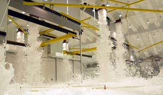 An Air Force hangar is filled with fire suppression foam system sprays during a test in Guam. (Image: U.S. Air Force) ** FILE **