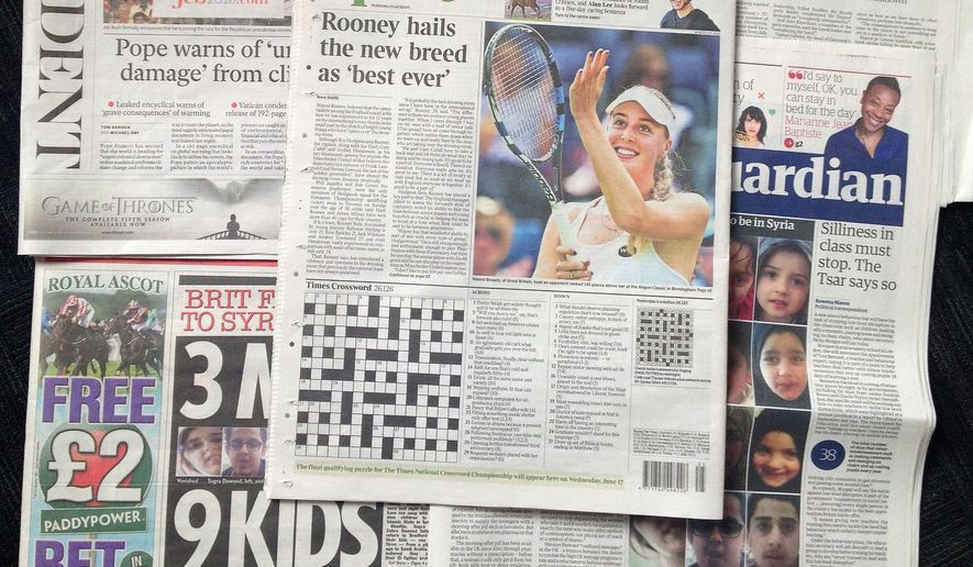 A combo taken on Wednesday June 17, 2015, shows some of the British national newspapers of Tuesday, June 16, and features at center the back page of The Times showing its daily crossword puzzle. A crossword-loving British lawyer hid a marriage proposal in Tuesday's edition of The Times newspaper's daily puzzle. (AP Photo/Tony Hicks)