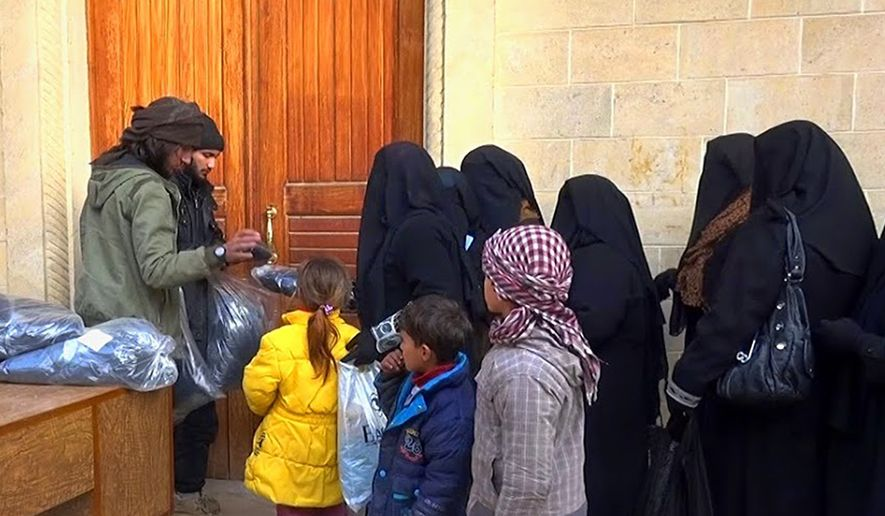 Members of the Islamic State group, left, distribute niqabs, enveloping black robes and veils that leave only the eyes visible, to Iraqi women in Mosul, northern Iraq, June 18, 2015. (Associated Press) ** FILE **