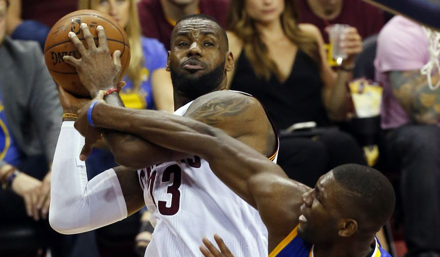 Cleveland Cavaliers forward LeBron James (23) is defended by Golden State Warriors center Festus Ezeli (31) during the second half of Game 6 of basketball's NBA Finals in Cleveland, Tuesday, June 16, 2015. (AP Photo/Paul Sancya)