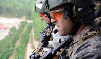 U.S. Special Forces (USSF) soldiers scan the ground below for threats while flying on a MH-60 Black Hawk during a Fast Rope Insertion Extraction System training exercise. USSF fast roped onto a specific target during the Special Forces Advanced Reconnaissance, Target Analysis, and Exploitation Techniques Course, John F. Kennedy Special Warfare Center and School on Fort Bragg, N.C., Aug. 28, 2012. (U.S. Army Photo by Sgt. Justin P. Morelli)