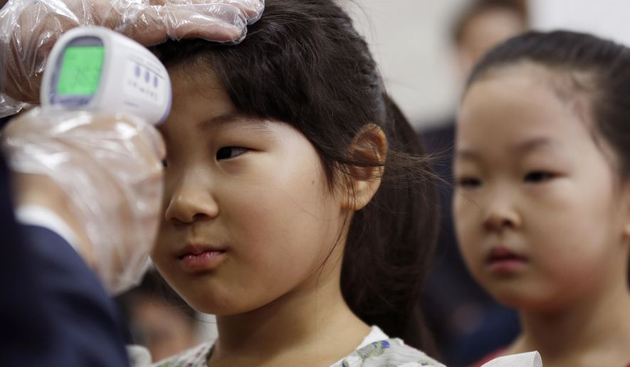 Au unidentified student is checked her temperature as a precaution against MERS (Middle East Respiratory Syndrome) at Gwanghui Elementary School in Seoul, South Korea, Wednesday, June 17, 2015. The death toll in South Korea's MERS outbreak increased Tuesday even as schools reopened and people recovered from the virus. (AP Photo/Ahn Young-joon)
