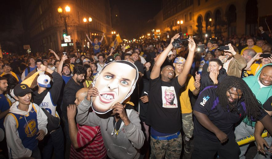 People celebrate in downtown Oakland, Calif.,  after the Golden State Warriors defeated the Cleveland Cavaliers 105-97 in Game 6 of the NBA Finals to win the championship, Tuesday, June 16, 2015, in Oakland, Calif.  (AP Photo/Noah Berger)