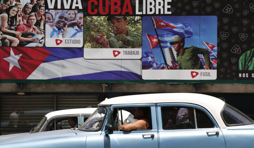 """A classic American car passes in front of some signs that reads in Spanish """"Long Live Free Cuba"""" in Havana, Cuba, Tuesday, June 16, 2015. Six months ago Wednesday, Presidents Barack Obama and Raul Castro stunned the world by announcing an end to their nations' half-century of official hostility. In Cuba, aging leaders fear swift, uncontrolled change that would cost them power and spawn disorder in a country that dreads the violence and inequality scarring its neighbors. That fear is heightened by the United States' long history of trying to topple Castro and his brother Fidel. (AP Photo/Desmond Boylan)"""
