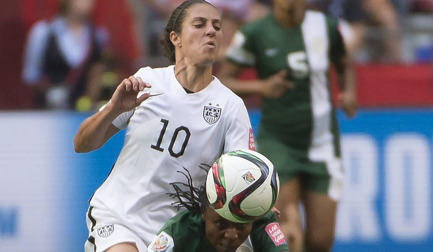 United States' Carli Lloyd (10) fights for control of the ball with Nigeria's Cecilia Nku (20) during the second half of a FIFA Women's World Cup soccer match, Tuesday, June 16, 2015 in Vancouver, New Brunswick, Canada (Jonathan Hayward/The Canadian Press via AP) MANDATORY CREDIT