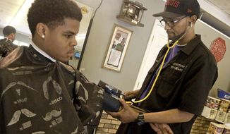 In this April 30, 2015 photo, Competitive Edge Barbershop owner Shon Allen (right) checks customer Elijah Kinmon's blood pressure before cutting his hair in Decatur, Ill. (Lisa Morrison/Herald & Review via AP) **FILE**