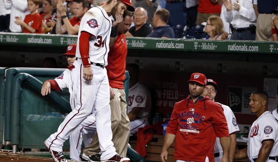 Washington Nationals right fielder Bryce Harper (34) leaves the field with head athletic trainer Lee Kuntz, rear, during the sixth  inning of a baseball game against the Tampa Bay Rays at Nationals Park, Thursday, June 18, 2015, in Washington. (AP Photo/Alex Brandon)