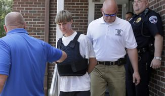Charleston, S.C., shooting suspect Dylann Storm Roof, center, is escorted from the Shelby Police Department in Shelby, N.C., Thursday, June 18, 2015. Roof is a suspect in the shooting of several people Wednesday night at the historic The Emanuel African Methodist Episcopal Church in Charleston, S.C. (AP Photo/Chuck Burton) ** FILE **