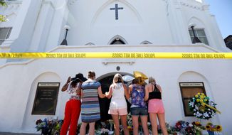 Women pray together at a makeshift memorial on the sidewalk in front of the Emanuel AME Church in Charleston, South Carolina, where nine people, including the church's pastor, were gunned down at a prayer meeting Wednesday evening. (Associated Press)