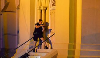 A police officer searches for a shooting suspect outside the Emanuel AME Church, in downtown Charleston, South Carolina on Wednesday. The shooting has prompted not just a calls for tighter gun-control laws, but also pleas from the right for churches to protect themselves by allowing their parishioners to carry concealed firearms. (Associated Press)