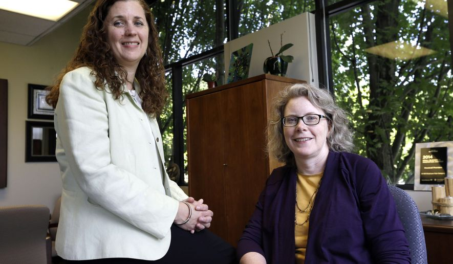 In this photo taken June 17, 2015, Dr. Pamela Miner, right, and nurse Mary Sayre pose for a photo at the Housecall Providers office in Portland, Ore.  The humble house call is being put to the test to see if it can improve care and cut costs for some of Medicare's most frail patients, and new data suggests it can work.   (AP Photo/Don Ryan)