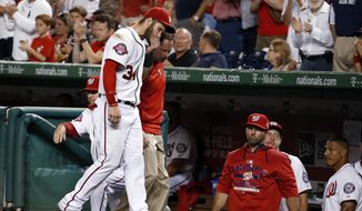Washington Nationals right fielder Bryce Harper (34) leaves the field with head athletic trainer Lee Kuntz, rear, during the sixth inning of Thursday night's game against the Tampa Bay Rays at Nationals Park in Washington. (Associated Press)