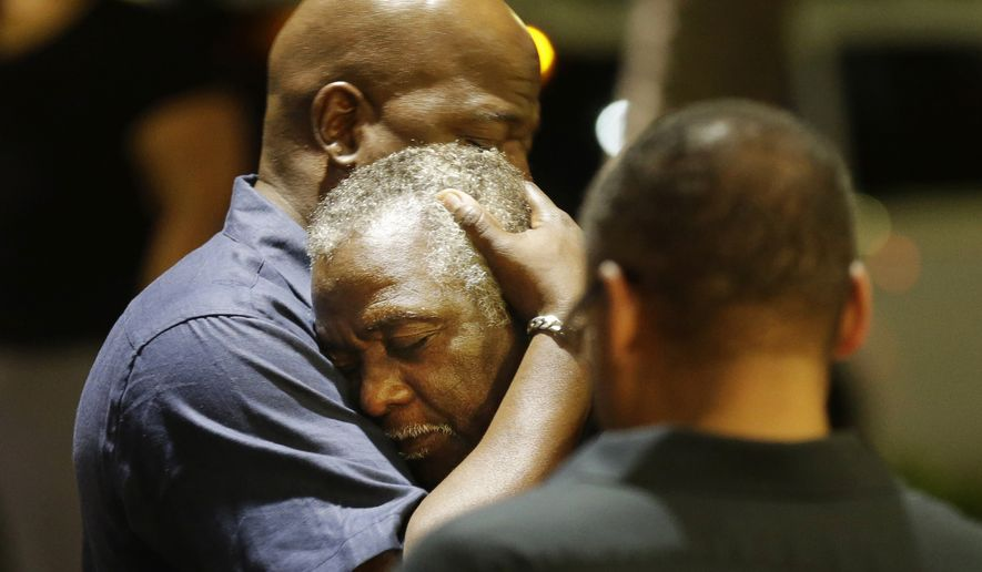 Worshippers embrace following a group prayer across the street from the scene of a shooting at Emanuel AME Church, Wednesday, June 17, 2015, in Charleston, S.C. A white man opened fire during a prayer meeting inside the historic black church, killing multiple people, including the pastor, in an assault that authorities described as a hate crime. (AP Photo/David Goldman) ** FILE **