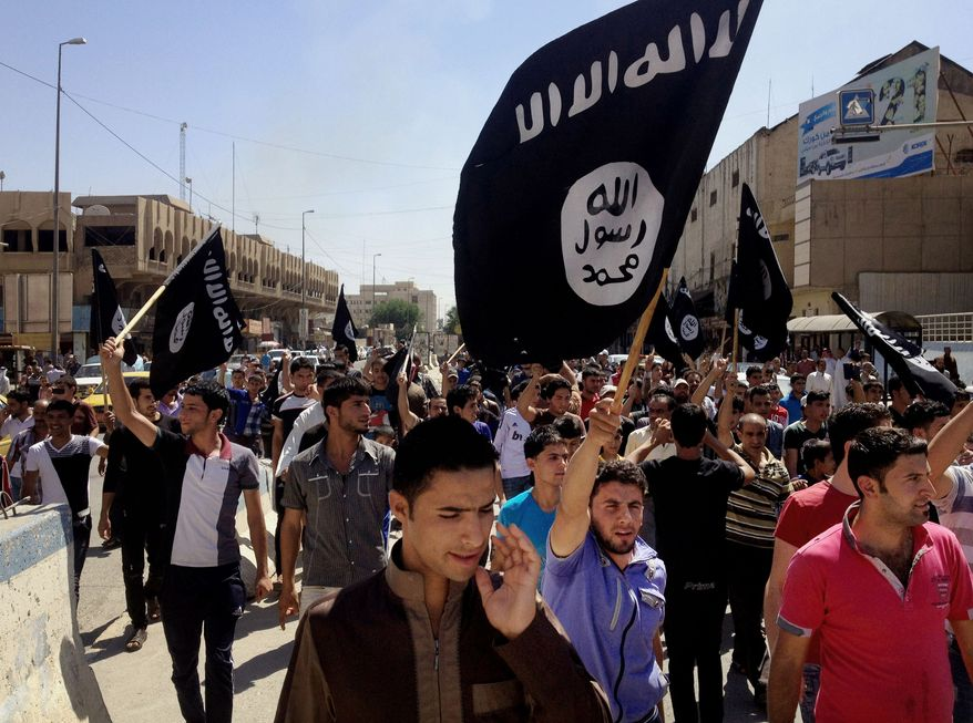 In this Monday, June 16, 2014 file photo, demonstrators chant pro-Islamic State group slogans as they wave the group's flags in front of the provincial government headquarters in Mosul, 225 miles (360 kilometers) northwest of Baghdad, Iraq. (AP Photo/File)