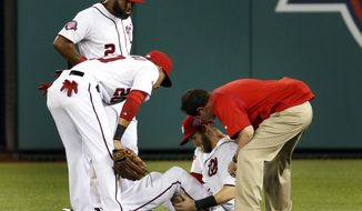 Washington Nationals' Ian Desmond (20) and center fielder Denard Span (2) look at right fielder Bryce Harper as he holds his left leg after an injury, as head athletic trainer Lee Kuntz, right, attends to Harper during the sixth inning of a baseball game against the Tampa Bay Rays at Nationals Park, Thursday, June 18, 2015, in Washington. Harper left the game. (AP Photo/Alex Brandon)