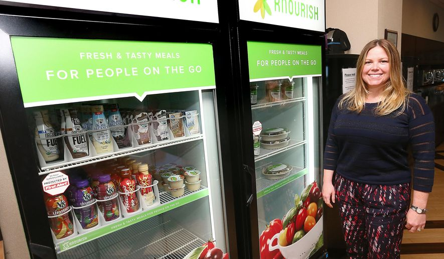 ADVANCED FOR RELEASE MONDAY, JUNE 22, 2015 Libby Spirer of the Waterfront restaurant in La Crosse, Wis., shows off the new Knourish vending machines in the LHI break room. Riverside Corporate Wellness has come up with healthy foods for the new vending service. (Erik Daily/La Crosse Tribune via AP)