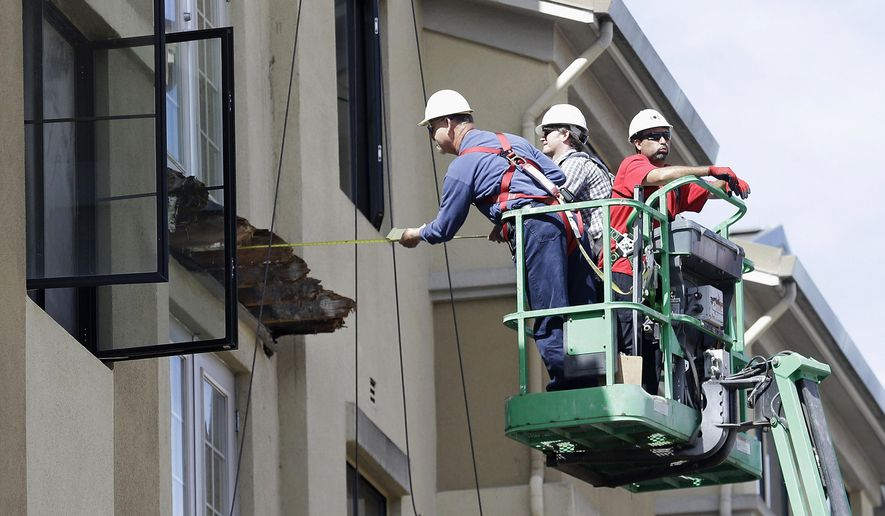 A worker measures near the remaining wood from an apartment building balcony that collapsed in Berkeley, Calif., Wednesday, June 17, 2015. The balcony broke loose from the building during a 21st birthday party early Tuesday, killing several people and seriously injuring others. (AP Photo/Jeff Chiu)