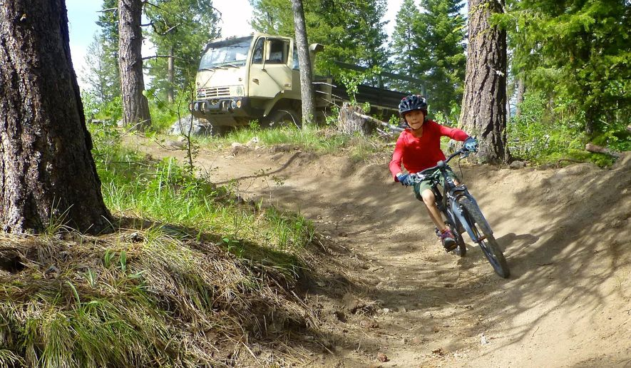 "This June 4, 2015 photo shows Jack Carey, 8, of McCall, Idaho, riding the new ""Berm and Ernie"" trail at Jug Mountain Ranch and that's Jug Mountain's shuttle vehicle in the background. (Roger Phillips/Idaho Statesman via AP) LOCAL STATIONS OUT (KTVB 7) MANDATORY CREDIT"