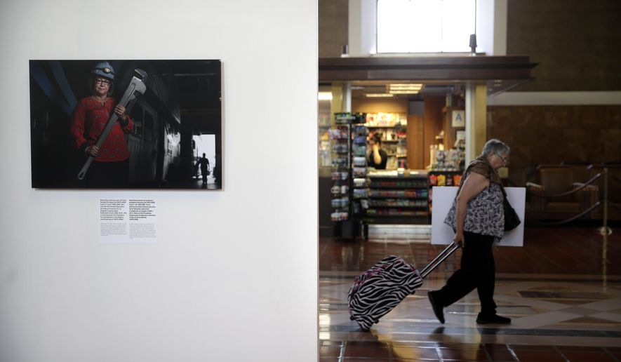 "In this Friday, June 12, 2015,  photo, a photo of Maria Elena Durazo, the first female president of UNITE HERE Local 11 from 1988 to 2006, photographed by Pulitzer Prize-winner Deanne Fitzmaurice, is displayed as part of an exhibit at Union Station in downtown Los Angeles.  The exhibit features 15 color photographs by Fitzmaurice juxtaposed against 25 World War II-era photos of ""Rosie the Riveter,"" the catchall name for the women who, with rivet guns and other tools in hand, kept American manufacturing running while their male counterparts were off fighting the war. (AP Photo/Jae C. Hong)"