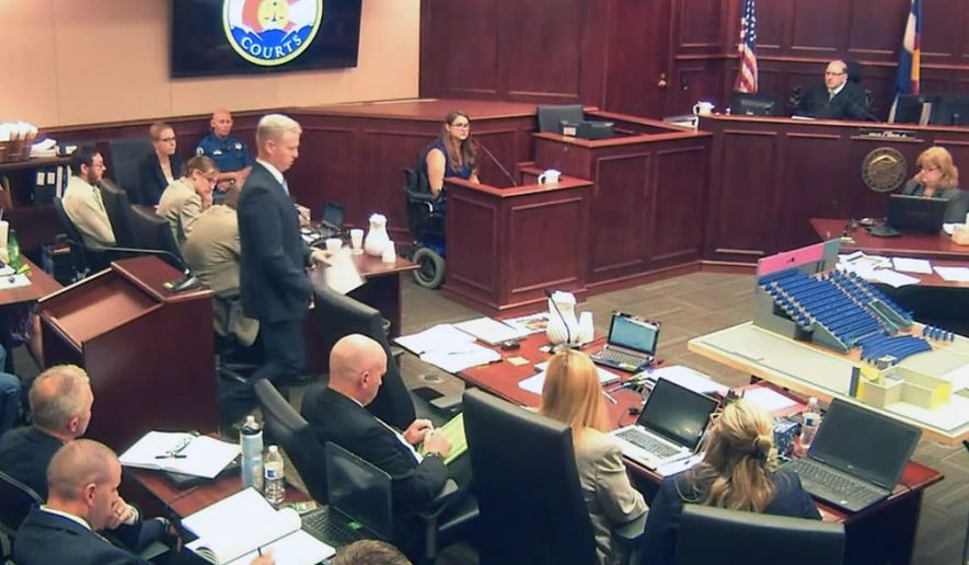 In this image taken from video, Ashley Moser, center top, who lost her 6-year-old daughter Veronica, was paralyzed, and suffered a miscarriage in the 2012 Colorado movie theater mass shooting, testifies during the trial of theater shooter James Holmes, pictured at top left, in Centennial, Colo., Friday, June 19, 2015. With Moser's testimony, the prosecution rested its case, led by District attorney George Brauchler, pictured fifth from left standing. (Colorado Judicial Department via AP, Pool)