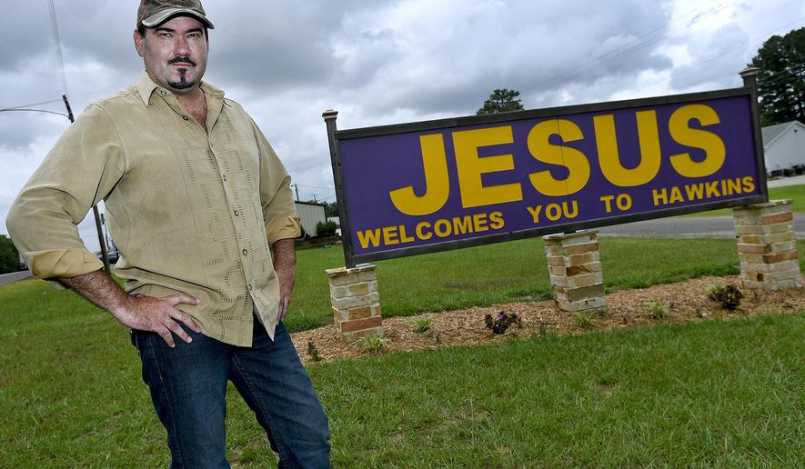 """Hawkins, Texas, Mayor Will Rogers poses Tuesday, June 16, 2015, with a sign welcoming visitors to the small Wood County community.  Rogers, who's been mayor for about a year, said he's ready for a fight after the city received a letter from the Wisconsin-based Freedom From Religion Foundation demanding the sign which reads """"Jesus Welcomes You To Hawkins"""" be moved off city property.  (Andrew D. Brosig/Tyler Morning Telegraph via AP MANDATORY CREDIT"""