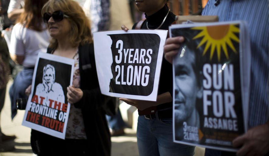 Supporters of WikiLeaks founder Julian Assange hold placards during a vigil across the street from the Ecuador embassy in London, Friday, June 19, 2015.  Julian Assange is marking the third anniversary of his stay inside Ecuador's London embassy. The WikiLeaks founder entered the building on June 19, 2012, to avoid extradition to Sweden for questioning about alleged sexual assaults. British police stand outside, ready to arrest him if he leaves. (AP Photo/Matt Dunham)