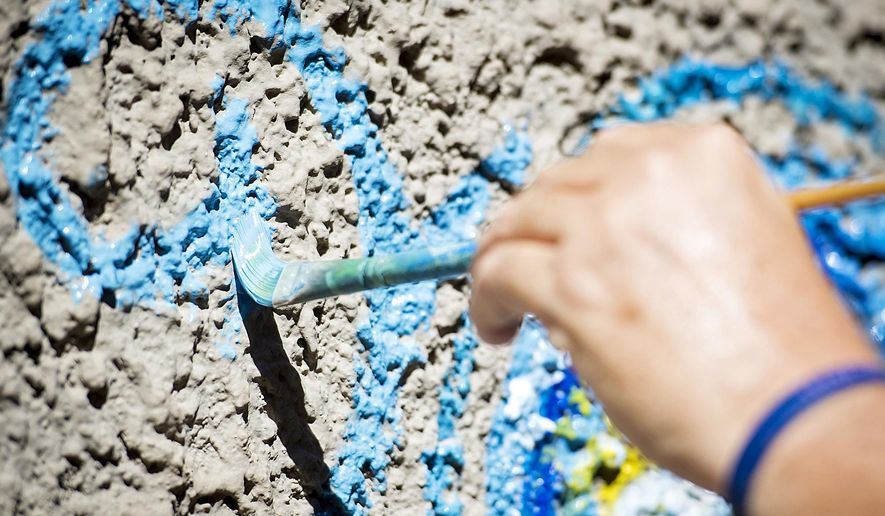 """Commissioned artist Mike Nelson paints a """"Starry, Starry Night"""" theme mural on the east exterior wall of the Creamery Building on Wednesday, June 17, 2015, in the alley just west of the Burkholder Project in the Haymarket.  (Kristin Streff/The Journal-Star via AP) LOCAL TELEVISION OUT; KOLN-TV OUT; KGIN-TV OUT; KLKN-TV OUT"""