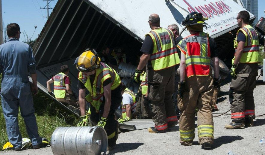 Firefighters remove kegs of beer after a semi-trailer tipped over on Fisher Road in Monitor Township on Friday, June 19, 2015. All barrels remained inside the truck after the accident and the driver was not hurt. (Nicole Hester/The Bay City Times via AP) LOCAL TELEVISION OUT