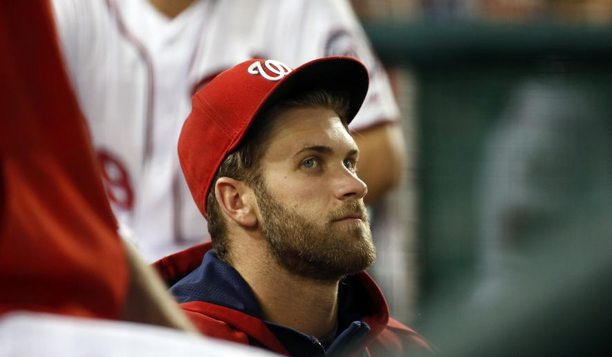 Washington Nationals right fielder Bryce Harper sits in the dugout during a baseball game against the Pittsburgh Pirates, Friday, June 19, 2015, in Washington. Harper injured his leg Thursday. (AP Photo/Alex Brandon)
