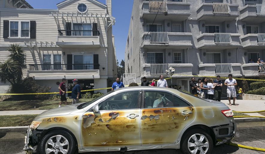 One of several cars damaged from the a blaze that gutted an unfinished apartment building sits in the Toluca Lake area of Los Angeles Friday, June 19, 2015. The blaze spread to an occupied complex and caused a woman to jump from the second story to escape the flames. (AP Photo/Damian Dovarganes)