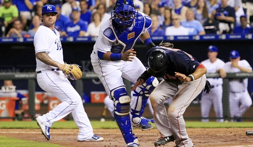 Boston Red Sox'  Mookie Betts, right, is tagged out by Kansas City Royals' catcher Salvador Perez, center, during a rundown as pitcher Brandon Fannegan provides backup in the seventh inning of a baseball game at Kauffman Stadium in Kansas City, Mo., Friday, June 19, 2015. Betts was caught attempting to score from third base. (AP Photo/Colin E. Braley)