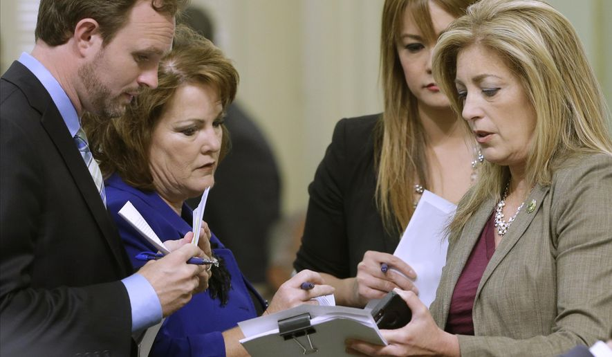 Republican Assembly members, from left, James Gallagher, of East Nicolaus, Shannon Grove, of Bakersfield, Ling Ling Chang, of Diamond Bar and Marie Waldron, of Escondido, confer before the Assembly takes up the revised budget plan at the Capitol in Sacramento, Calif., Friday, June 19, 2015.   Both houses of the Legislature approved the compromise spending plan and sent it to the governor.(AP Photo/Rich Pedroncelli)