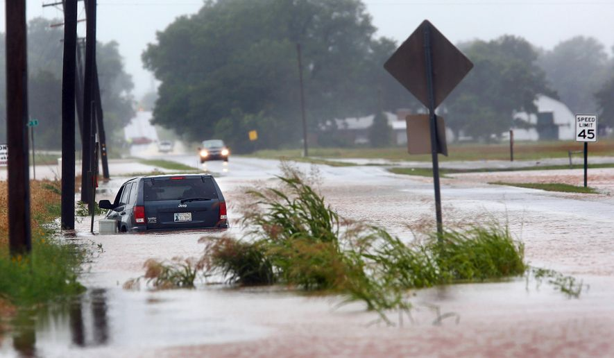 A vehicle is pointed the wrong direction after high water pushed it into a ditch on the south side of Hardesty Road west of US 177 in Shawnee, Okla. Rain from Hurricane Bill produced localized flooding in areas of Pottawatomie County on Thursday, June 18,  2015. (Jim Beckel/The Oklahoman via AP)