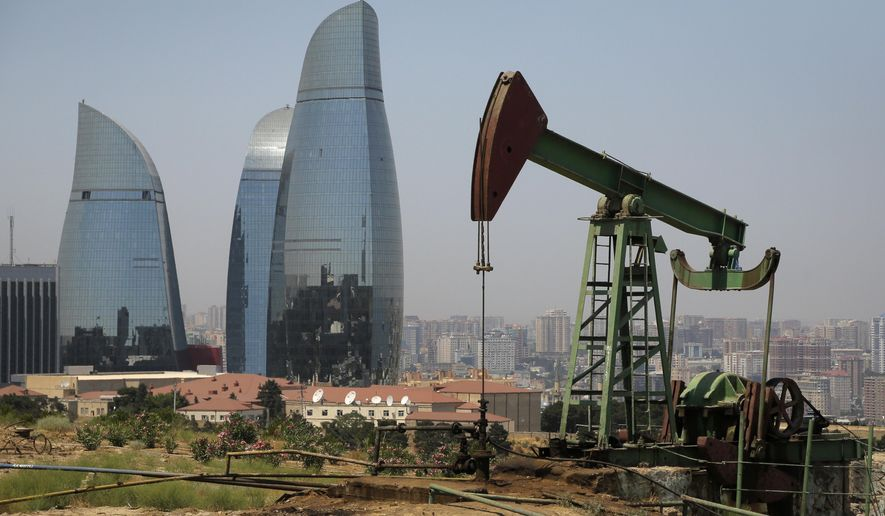 Skyscrapers stand in the background, as an oil pump works a nearby hill in Baku, Azerbaijan, Friday, June 19, 2015. The 2015 European Games are held in Baku till June 28. (AP Photo/Dmitry Lovetsky)