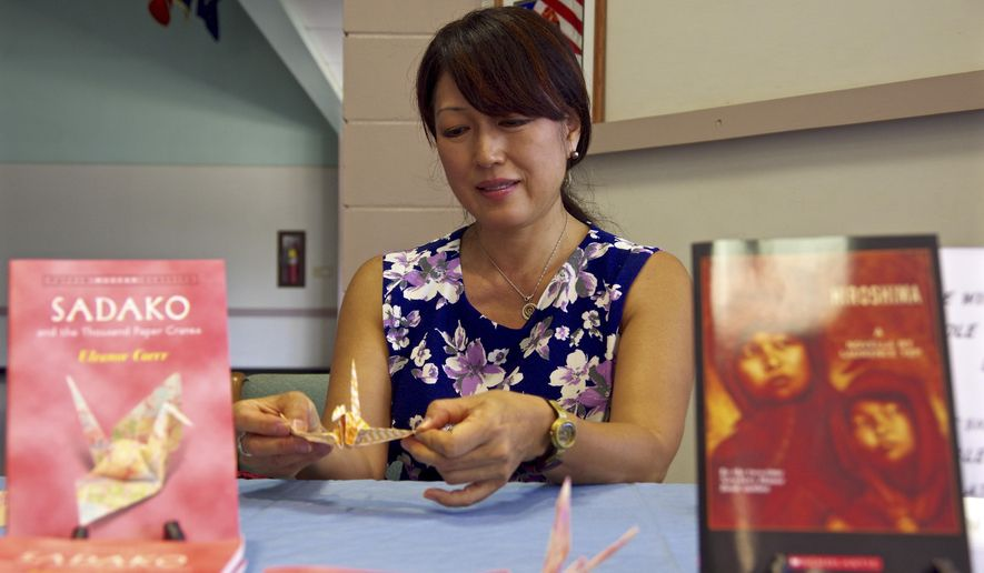 ADVANCE FOR SATURDAY JUNE 20, 2015 AND THEREAFTER- In this Monday, June 15, 2015 photo, Rev. Nicole Sakurai of the Happiness Planting Center is flanked by books on Sadako and Hiroshima as she makes a paper crane during the opening day of the Sadako and Thousand Paper Cranes exhibit at the Kauai Veterans Center in Lihue, Hawaii. The exhibit is an effort to raise peace awareness for the upcoming generations by providing visitors an opportunity to learn more about the effects the atomic bomb has on humanity. (Dennis Fujimoto/The Garden Island via AP)