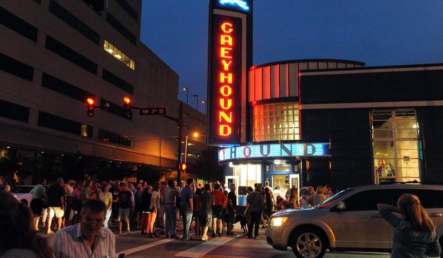 The neon lights are re-light as a large crowd gathers around the old Greyhound Station in Downtown Evansville, Ind., Thursday, June 18, 2015.  A crowd of about 500 people cheered  when the blue and amber neon lights were relit on the building's exterior, which is covered by two-toned blue porcelain enamel panels. (Jason Clark/Evansville Courier & Press via AP)