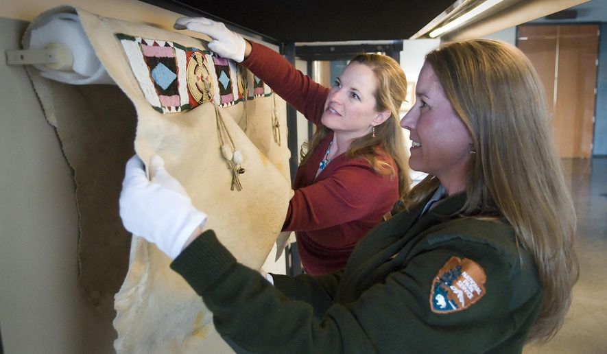 In this May 1, 2013 photo, Grand Teton National Park museum curator Bridgette Guild, right, installs a Nez Perce blanket with display designer Suzanne McGarraugh at the Craig Thomas Discovery and Visitor Center in Moose, Wyo. (Bradly J. Boner/Jackson Hole News & Guide via AP)