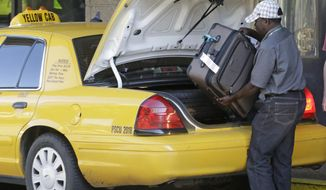 A taxi driver loads luggage from a traveler into the back of his taxi. (AP Photo)