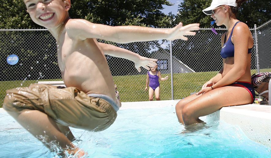 In a Tuesday, June 9, 2015 photo, lifeguard Kassie Bain watches over swimmers in the kiddie pool at Moville, Iowa, as Steven Procko, 7, jumps in the water. (Jim Lee/ Sioux City Journal via AP)